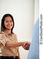 Ethnic young businesswoman giving hands greeting