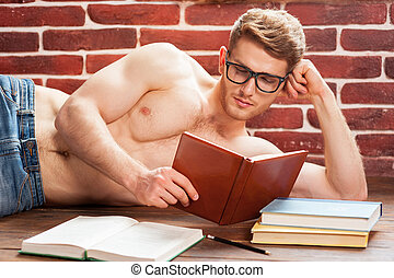 Reading his favorite book. Thoughtful young shirtless man...