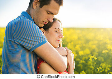 Couple in love in field - Happy young couple in love hugging...