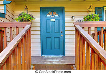 Entrance porch with blue door and stairs with railings