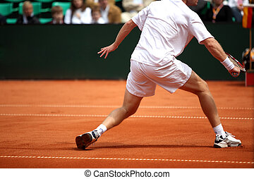 Racket - A man is returning a ball during a tennis match...