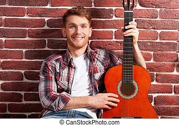 I love my guitar. Handsome young man holding acoustic guitar...