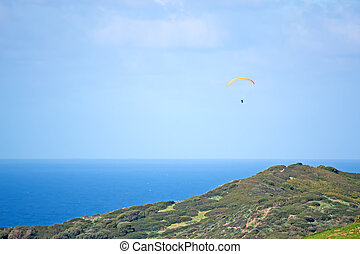 gliding over the sea - para glider flying on a clear day