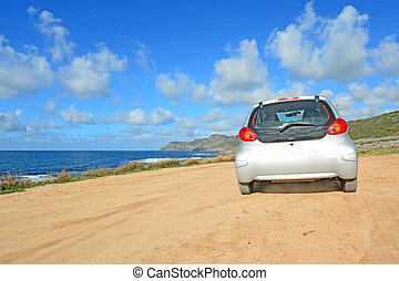 gray car in a dirt road by Argentiera shore with para...