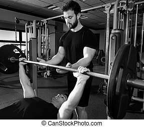 Bench press weightlifting man with personal trainer in...