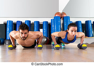Dumbbells push-ups couple at fitness gym - Dumbbells...