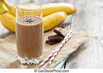 Chocolata banana smoothie in a glass with straws