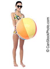 Smiling woman in bikini holding a beach ball