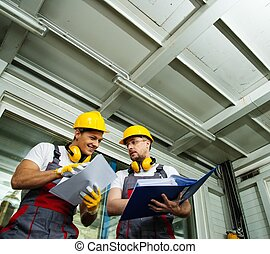 Two workers in a factory control room reading documentation...