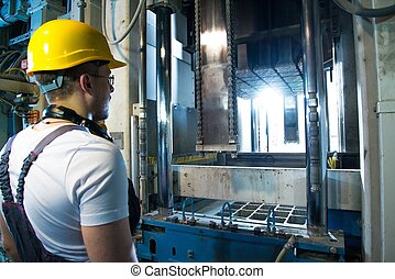 Worker in safety hat near machine on a factory