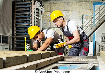 Worker and foreman in a safety hats performing quality check...