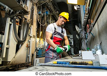 Worker in safety hat in machinery room on a factory
