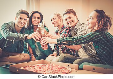 Group of young multi-ethnic friends with pizza and bottles...
