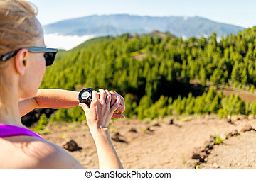 Cross country runner looking at sport watch - Runner on...