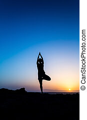 Woman doing yoga sunset silhouette - Young woman doing...