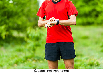 Trail runner looking at sport watch - Runner on mountain...