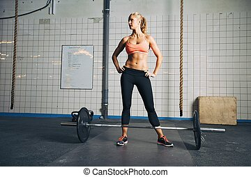 Strong crossfit female at gym with barbells - Full length...