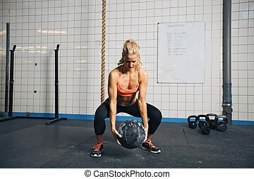 Woman doing crossfit workout with medicine ball at gym - Fit...