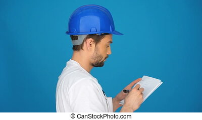builder writing down notes - builder in hat writing down...