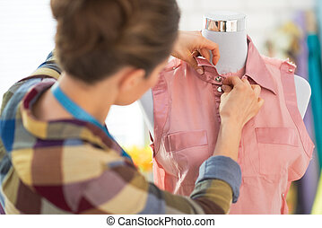 Seamstress adjusting clothing on mannequin rear view