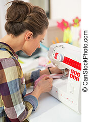 Seamstress working with sewing machine rear view