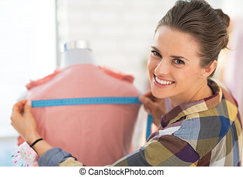 Happy seamstress measuring garment on mannequin