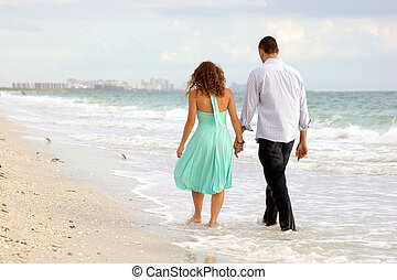 A young couple walking hand in hand along the beach, their feet ate in the water, they have their backs to the viewer, there are birds on the beach and a city in the background