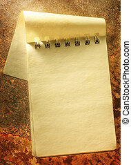 Blank open yellow notepad on rusty background