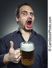 Happy man drinking beer from the mug - Satisfied man with...