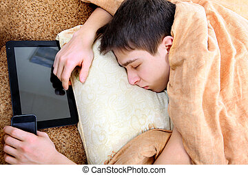Teenager sleeps with Tablet - Tired Teenager sleeping at the...