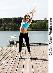 Woman exercising outdoors - Young woman working out outdoors