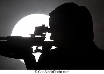Shooting - Silhouette of a woman training sport shooting...