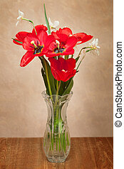 Bouquet of red tulips and daffodils in a vase