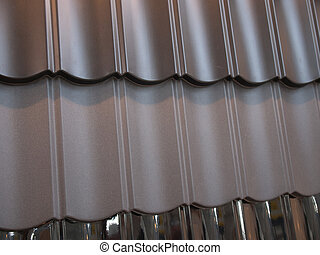 Fragment of modern metal roof tiles in different colors