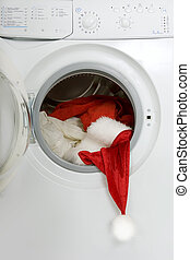 Christmas wash: washing machine with a red Santa suit -...