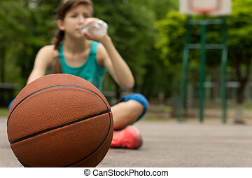 Young basketball player drinking water as she sits...