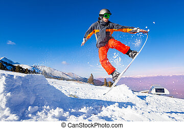 Snowboarder holding board during jump - Snowboarder holding...