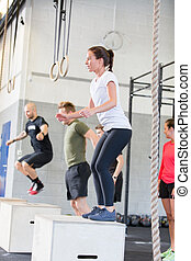 Crossfit group trains box jumps - A group trains at a...
