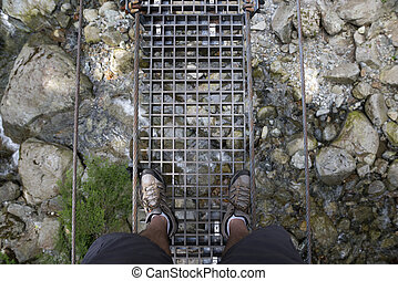 Foot bridge with metal grid (flood) and walkers legs