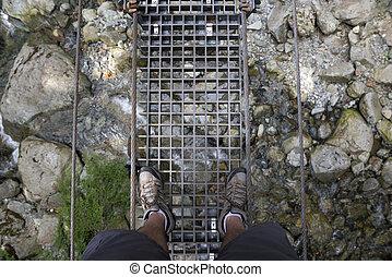 Foot bridge with metal grid (flood) and walkers legs