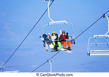 Three young people with snowboarders on ropeway - Three...