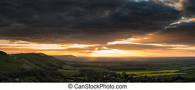 Stunning Summer sunset across countryside landscape with dramati