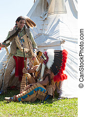 Two North American Indians communicate near a wigwam