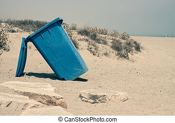Wheelie bin on sandy coast - Blue plastic Waste container on...