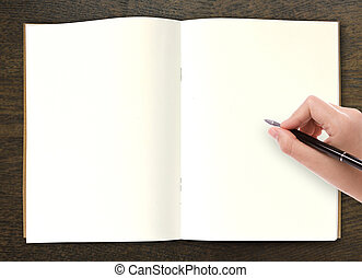 Hand writing in open book on table