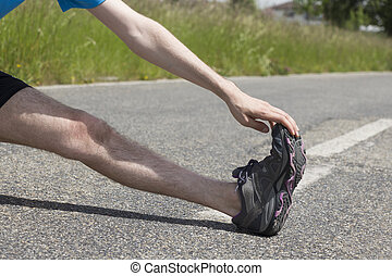 Closeup of a jogger stretching his legs - Runner man is...
