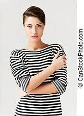 Staying hip. Fashionable young short hair woman in striped...