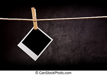 Photography paper with instant photo frame attached to rope with clothes pins. Copy space for your image.
