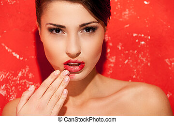 Back to natural. Portrait of beautiful young shirtless woman standing against red background and removing make-up