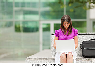 businesswoman using laptop outdoors - mixed-race business...